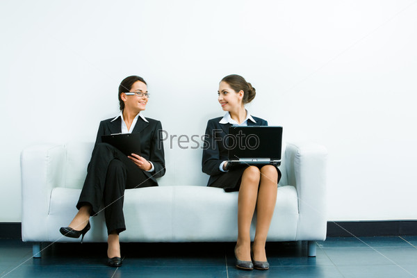 Image of two businesswomen wearing suits sitting on the white sofa