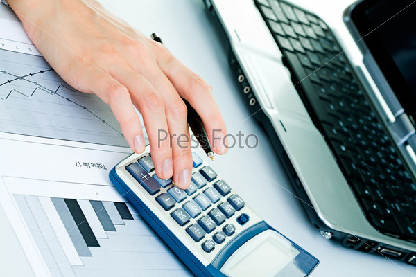 Пальцы деловой женщины, нажимающей на кнопки калькулятора