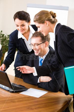 Group of three confident business people looking at the monitor of laptop
