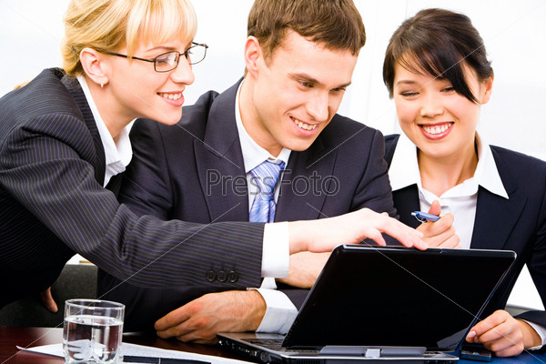 Three business people gathered together around the table discussing computer work