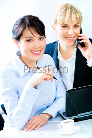 Image of two confident business women sitting at the table