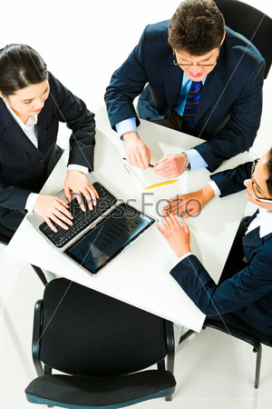 Photo of three business people sitting at the table with laptop, pens, notepad on it