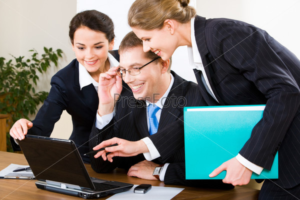 Photo of business woman explaining a computer work to her colleagues
