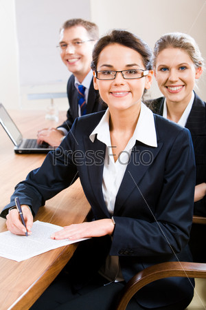 Image of business team with leader in front sitting at the table