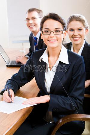 Деловая команда сидит за столом с лидером впереди