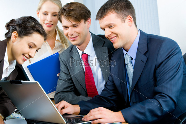 Four business persons gathered together looking at monitor of laptop