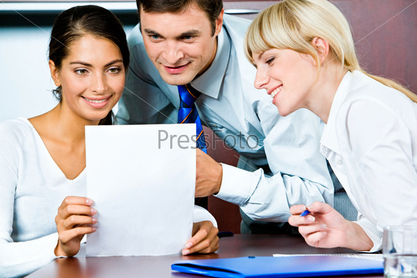 Image of confident business persons looking at the document
