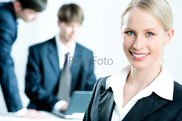 Portrait of confident smiling woman in suit on the background of men