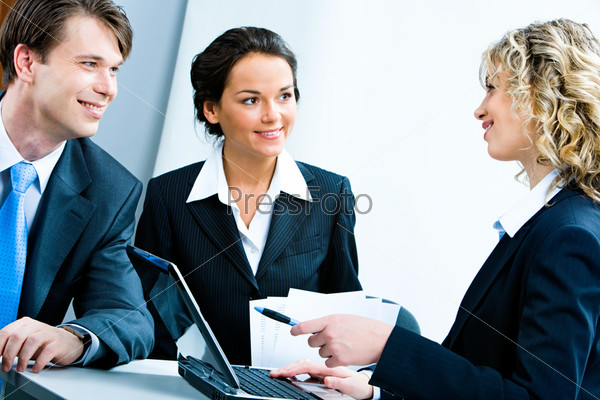 Image of business persons listening to woman speaking about her work