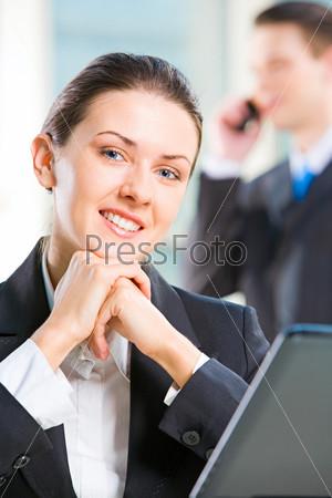 Деловая женщина опирается подбородком на руки