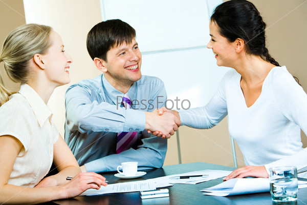Image of business partners shaking hands at business meeting