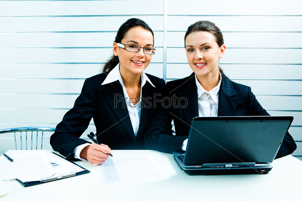 Portrait of two pretty white-collar workers sitting at the table
