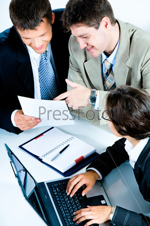 Тwo businessmen discussing business plan while business lady typing document