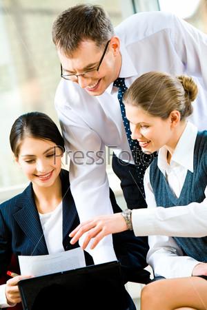 Три деловых партнера смотрят с улыбками в бизнес-план