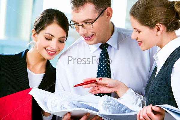 Вusinessman and two businesswomen looking at business plan and reading it