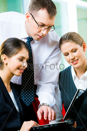 Portrait of three specialists looking at the laptop screen at business meeting