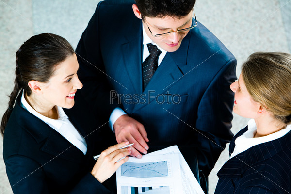 Тhree confident colleagues discussing growth rates of business sales