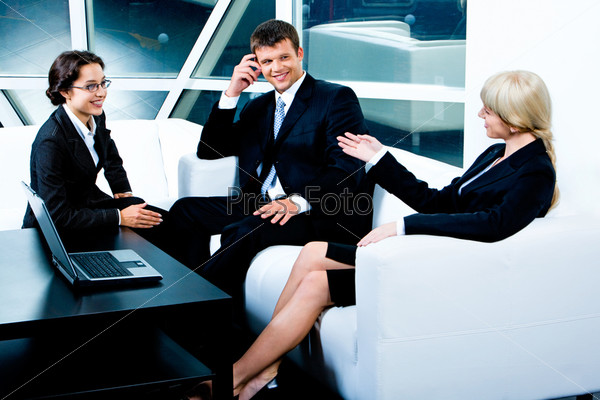 Image of three business partners sitting on white sofa near the table