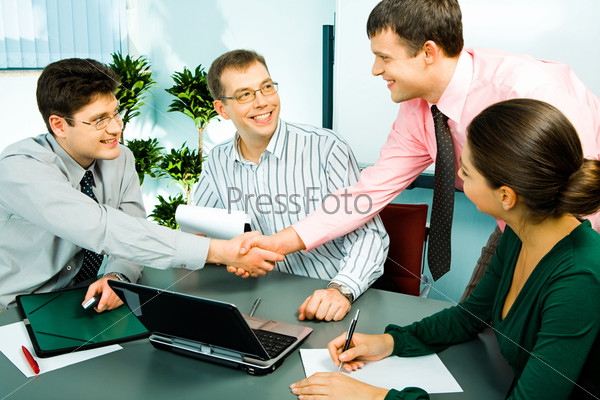 Photo of handshake of businesspeople with their smiling colleagues sitting near by
