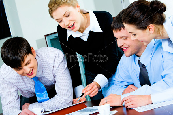 Group of four happy business partners looking at business plan lying on the table