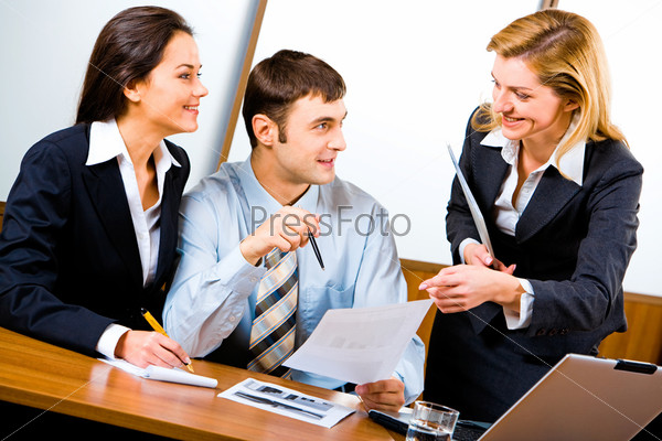 Two smiling business partners looking at confident business lady