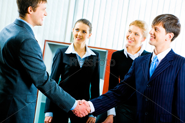 Portrait of two businessmen shaking hands and looking at each other with smiles