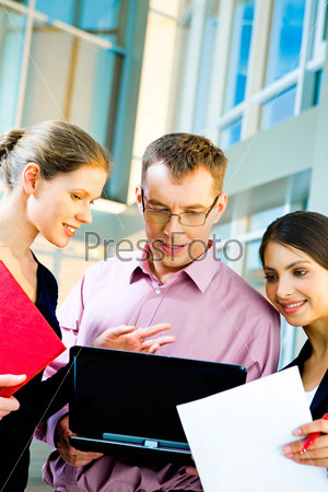 Vertical photo of successful businessteam working on the laptop in the office