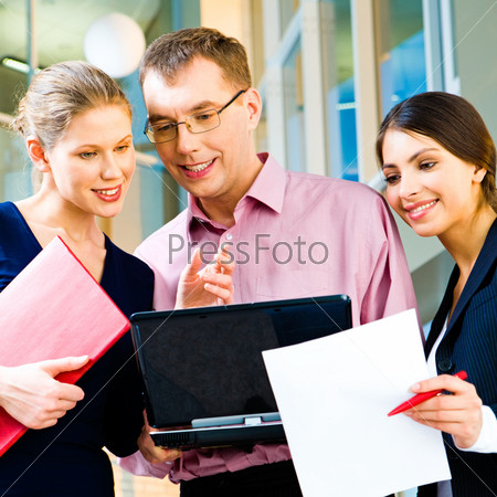 Portrait of a business group looking at the screen of laptop with smiles