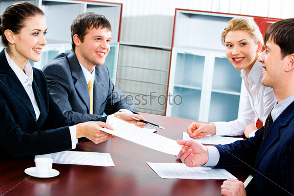 Portrait of several business partners sitting at the table in the office