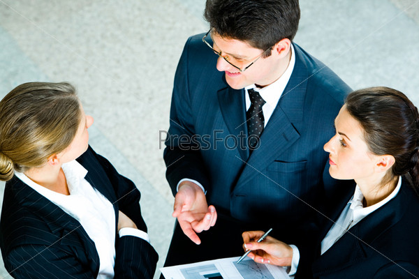 speaking business partners with a pretty assistant holding document and pen