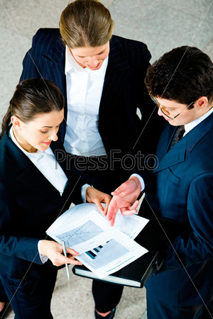 Businesspeople discussing business documents with their partner standing near by