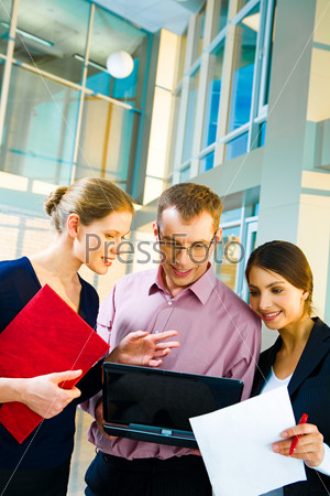 Photo of confident specialists standing and looking into the monitor of laptop