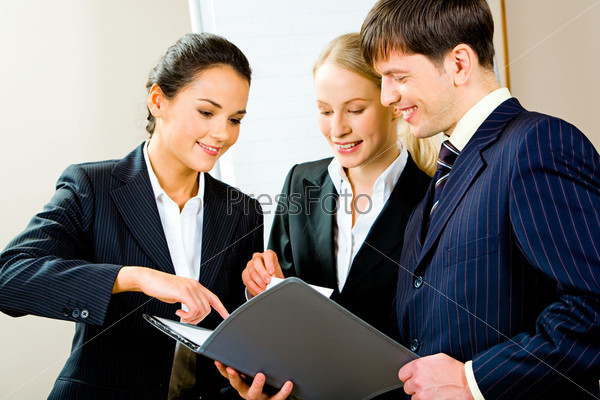 Portrait of three smiling young specialists looking at business plan