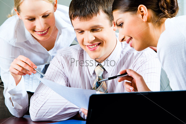 Portrait of a businessman  with two beautiful smiling business ladies near by