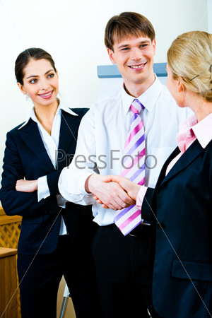 Portrait of smiling businessman shaking his co-worker's hand at meeting