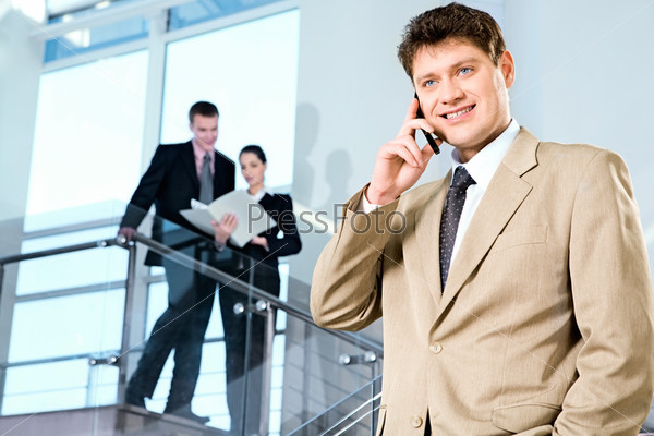 Portrait of confident manager calling by cellphone on the background of people