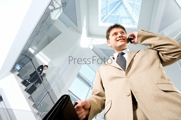 Image of busy successful man in suit in the modern office block