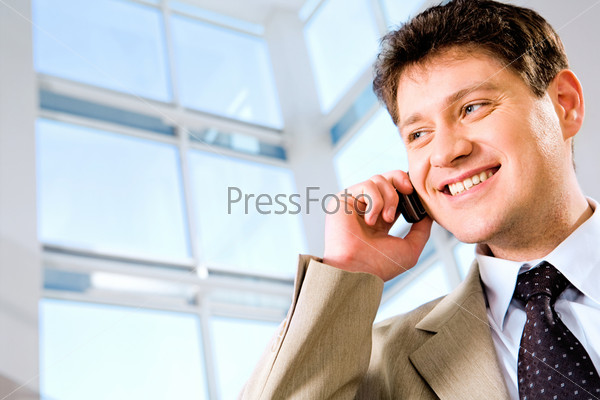 Image of business man calling by phone on the background large window