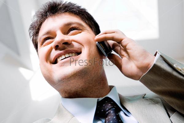 Лицо бизнесмена, говорящего по телефону с улыбкой