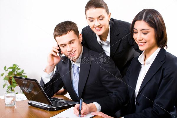 Три деловых партнера работают в офисе, смотря в бизнес-план