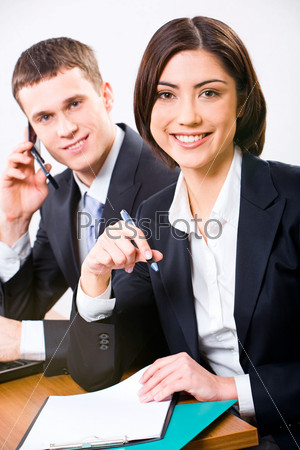 Рretty businesswoman doing paperwork while businessman speaking on cellphone