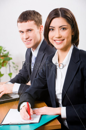 Portrait of a beautiful smiling girl sitting in the office with a confident businessman