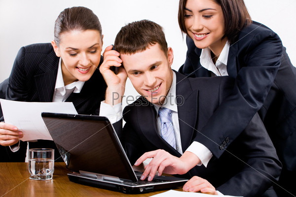 Three businesspeople looking at the screen of laptop with smiles