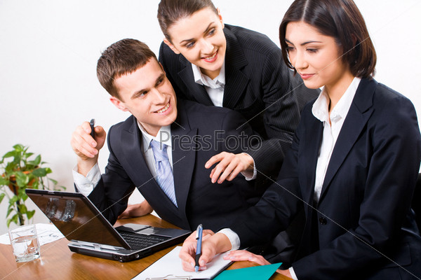 secretary writing something in her notebook while two businesspeople looking at her
