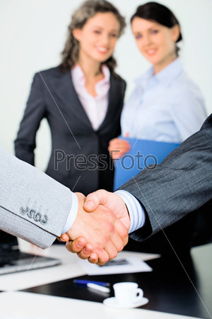 Vertical image of handshake of businessmen on the background of two women