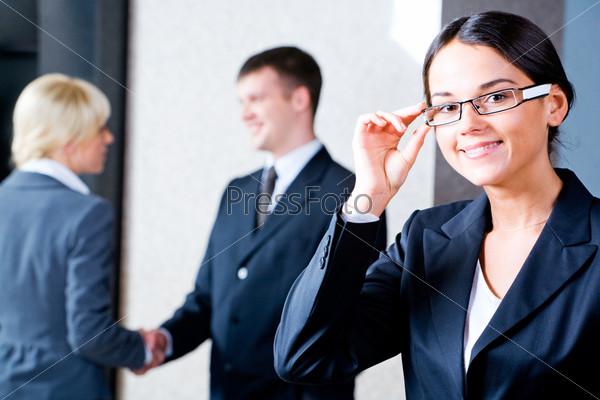 Уверенная деловая женщина в очках стоит в офисе