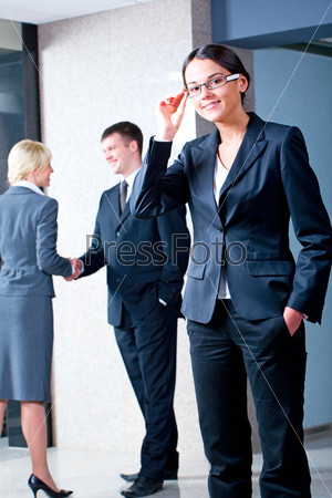 Portrait of confident businesswoman with glasses standing in the office