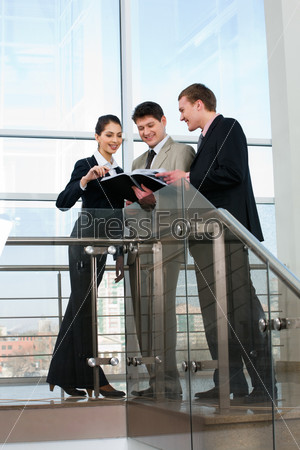 Portrait of business people looking at document in the corridor