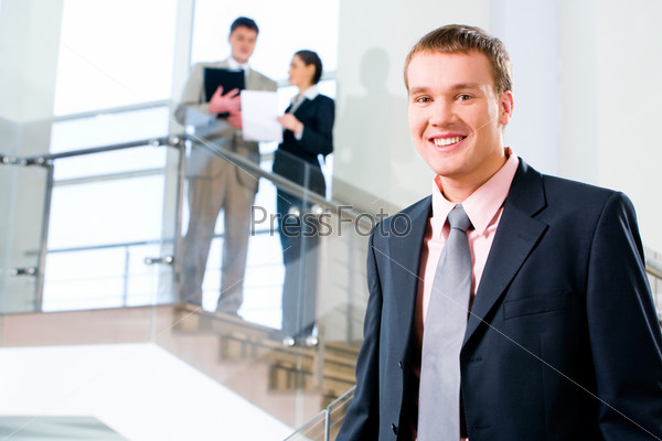 Portrait of handsome businessman in suit on the background of people
