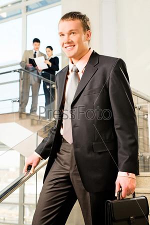 Красивый бизнесмен спускается вниз по лестнице
